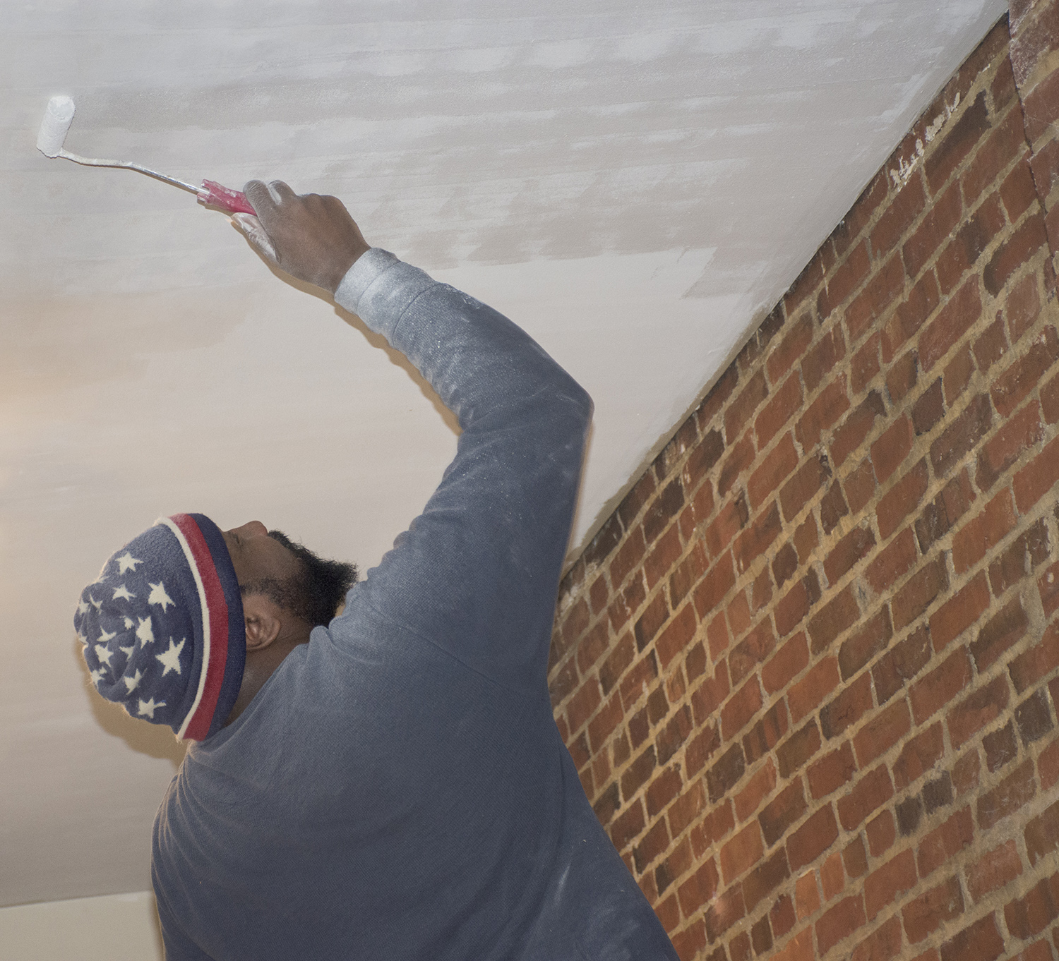 Robert Lee Jr. paints a ceiling on the second floor of the building at 1100 Hollins Street