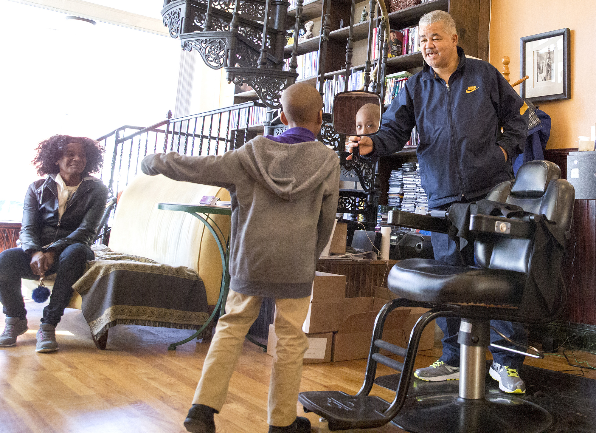 RIcky Phaison holds a mirror so a young customer can check his haircut. Photo by Antonella Crescimbeni
