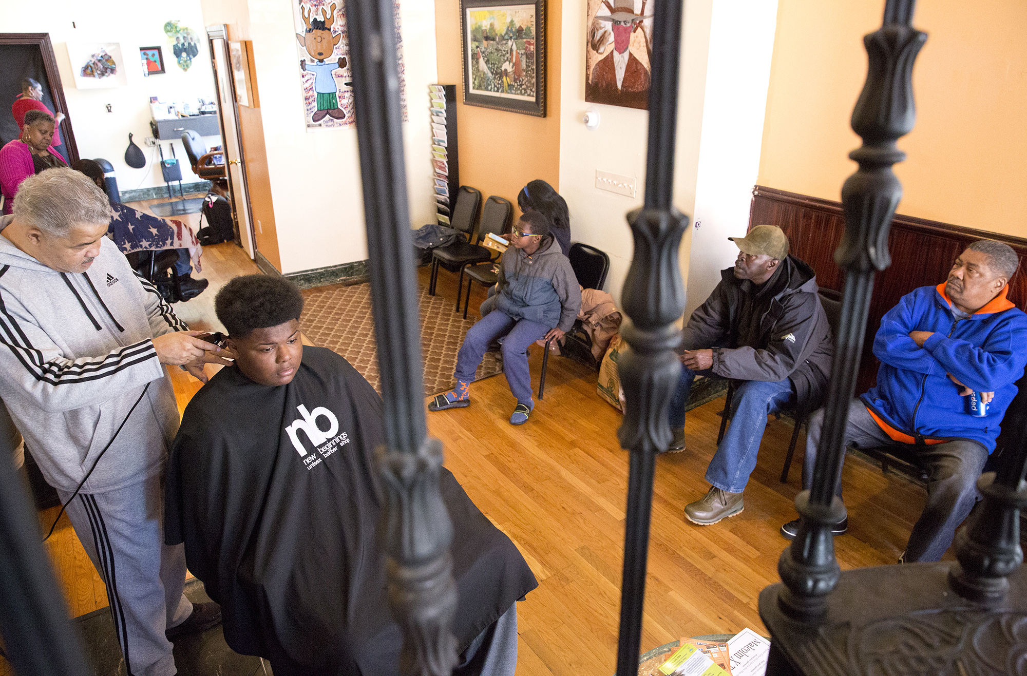 Ricky Phaison and a young customer are framed by the ornate metalwork on the spiral staircase at New Beginnings Unisex Barbershop. Photo by Antonella Crescimbeni