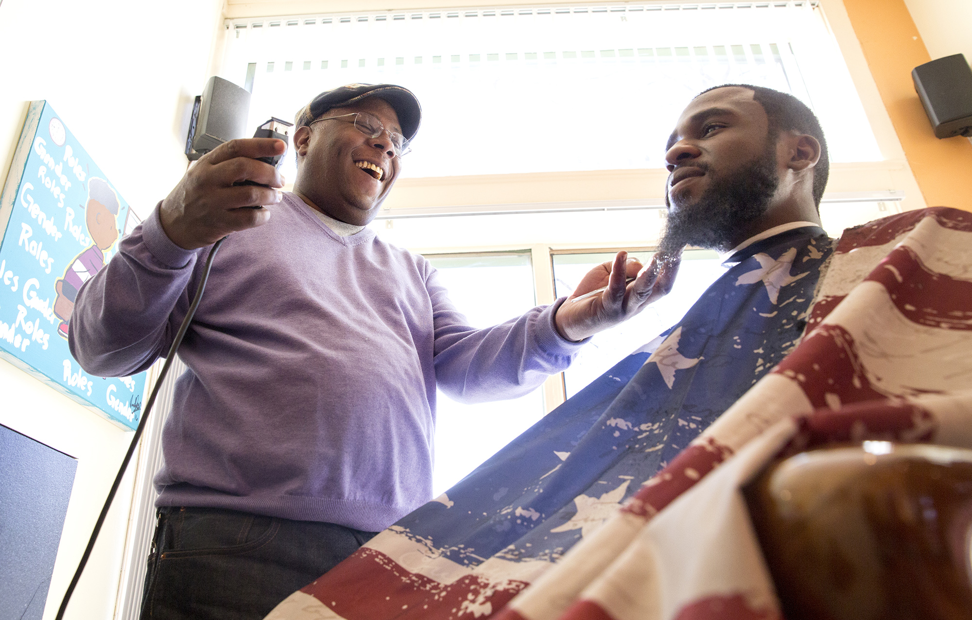 Troy Staton shares a story with long-time customer Brandon Cofield a New Beginnings Unisex Barbershop. Photo by Antonella Crescimbeni