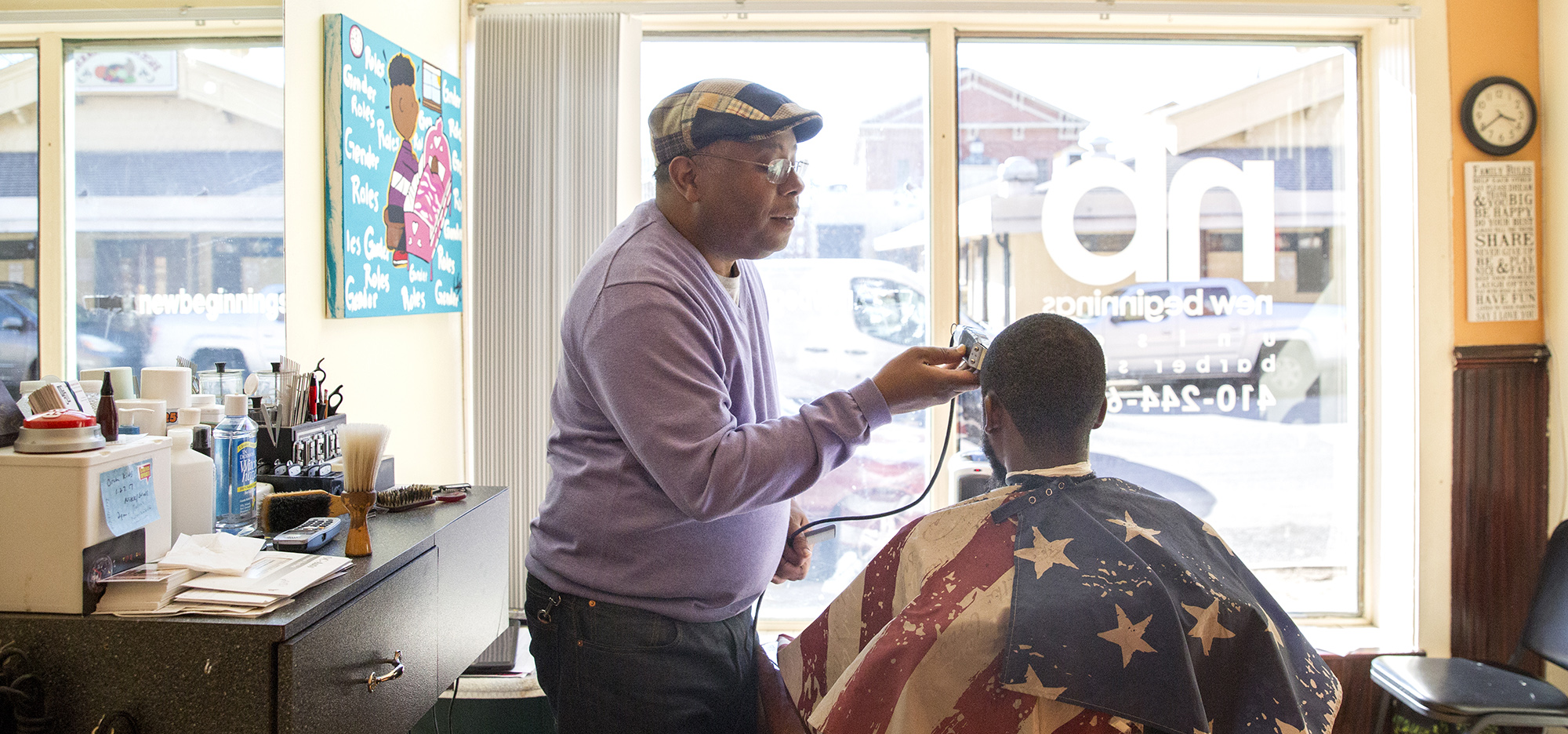 Hollins Market, across the street, and a Jerrel Gibbs painting on the wall exemplify the mix of commerce and culture available at New Beginnings Unisex Barbershop, where Troy Staton has a customer in the chair. Photo by Antonella Crescimbeni