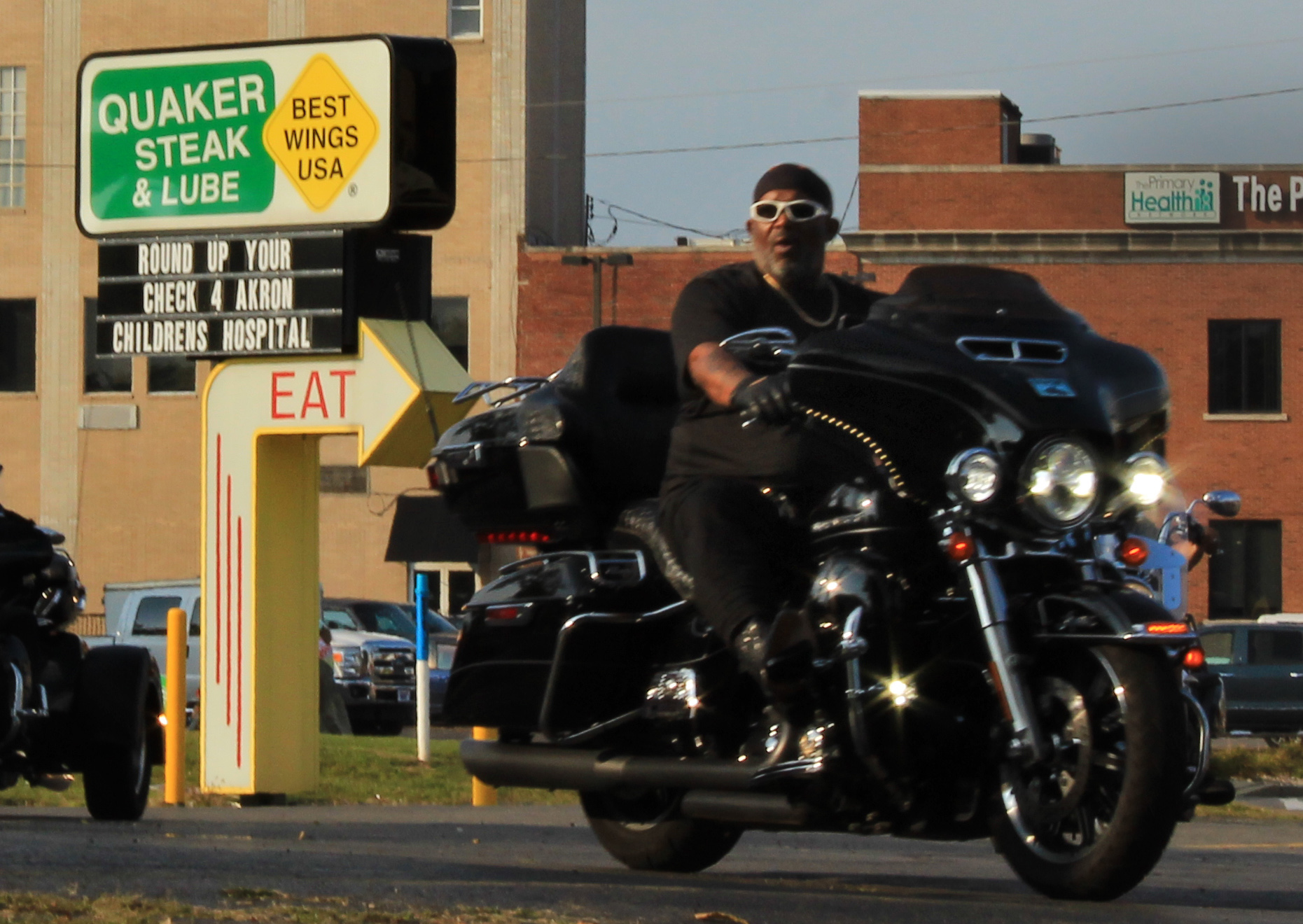 A cyclist motors past Quaker Steak and Lube in Sharon. This motor-themed restaurant is the original Quaker Steak and Lube. It was opened in 1974, and is still known for its wings and Bike Night. The restaurant anchors one end of the three block section of the Shenango River that hosts the Waterfire festivities. Photo by Teagan Staudenmeier