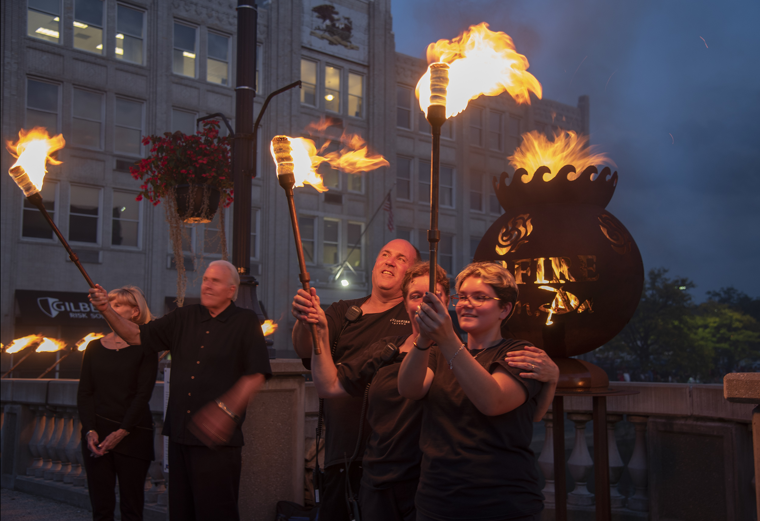 The members of two families hold their torches aloft after lighting the Waterfire Sharon orb. From left are: Gayle and Ron Anderson, and Rick, Jen and Emma Barborack. Photo by Risell Ventura