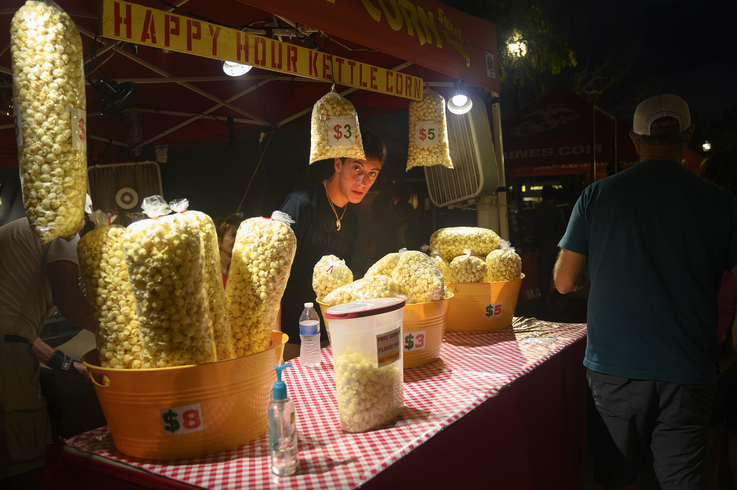 A Waterfire vendor waits for customers at Happy Hour Kettle Corn. Photo by Jade Campos