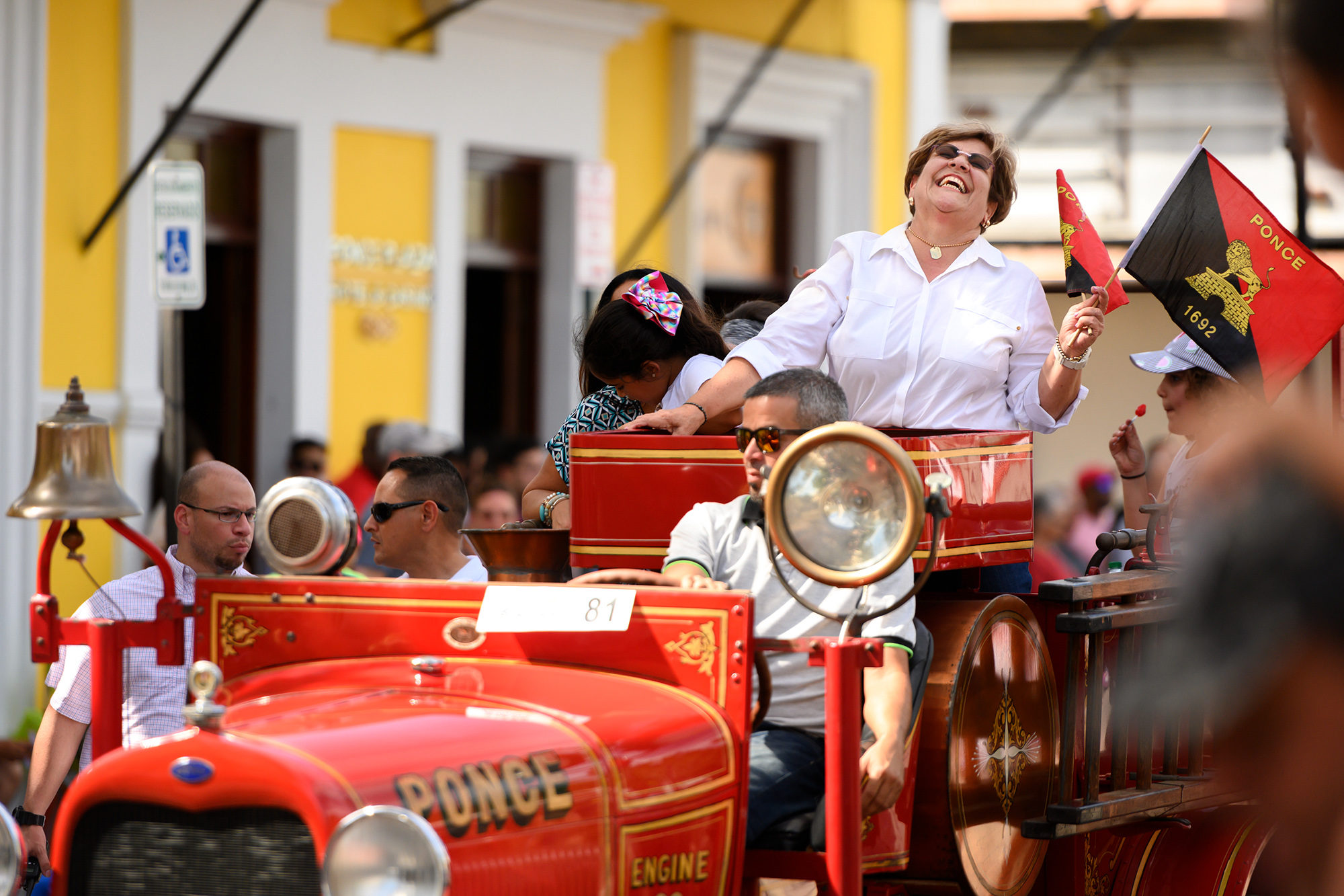María Meléndez, the mayor of Ponce, Puerto Rico, laughs on the back of an antique firetruck during the Carnaval Ponceño parade in Ponce on Sunday, March 3, 2019. Photo by Sydney Herdle.