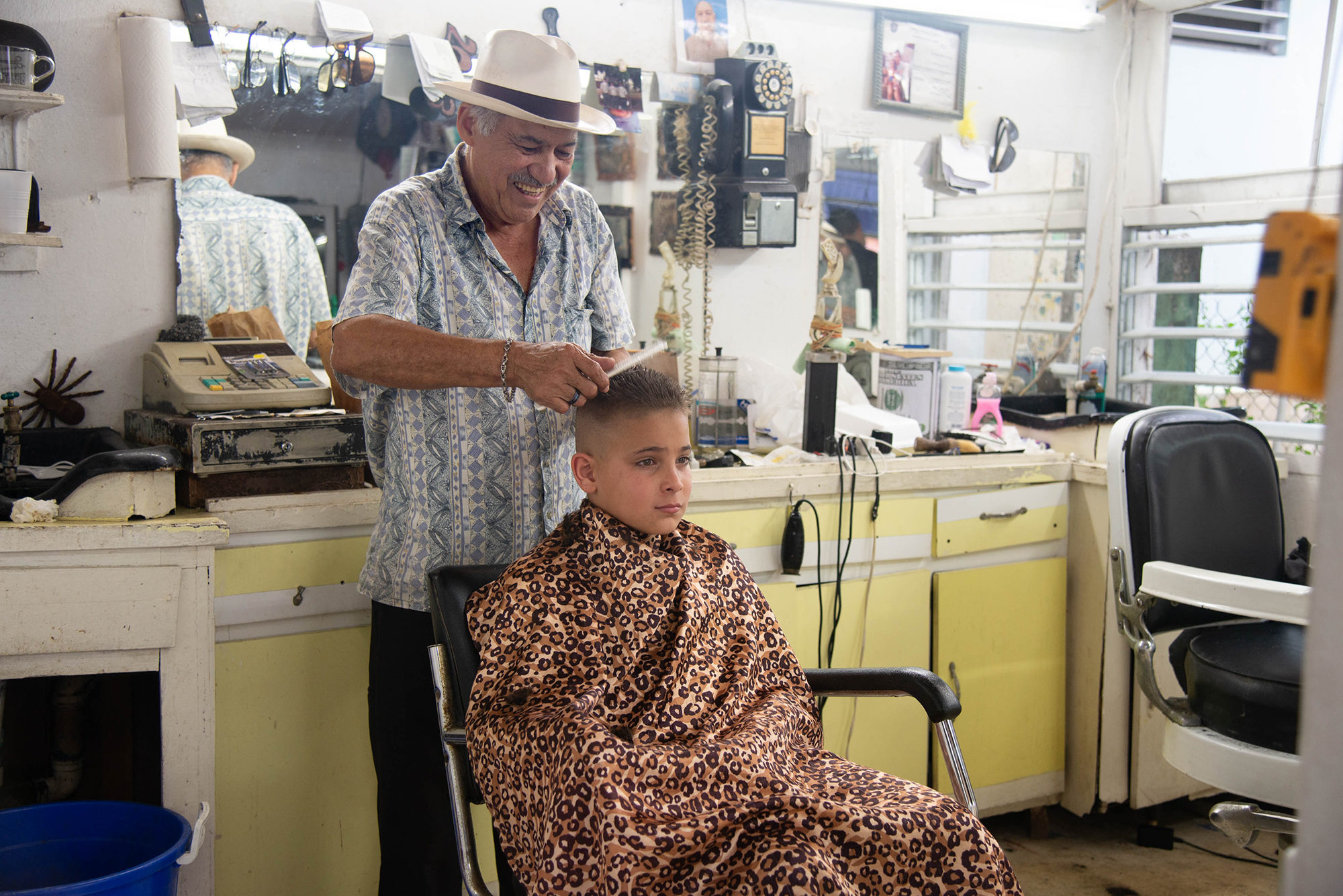 Joshua A. Gonzalez Feliciano gets a haircut from Orlando Perez at his solar-powered barber shop in Adjuntas. Photo by Valerie Welch