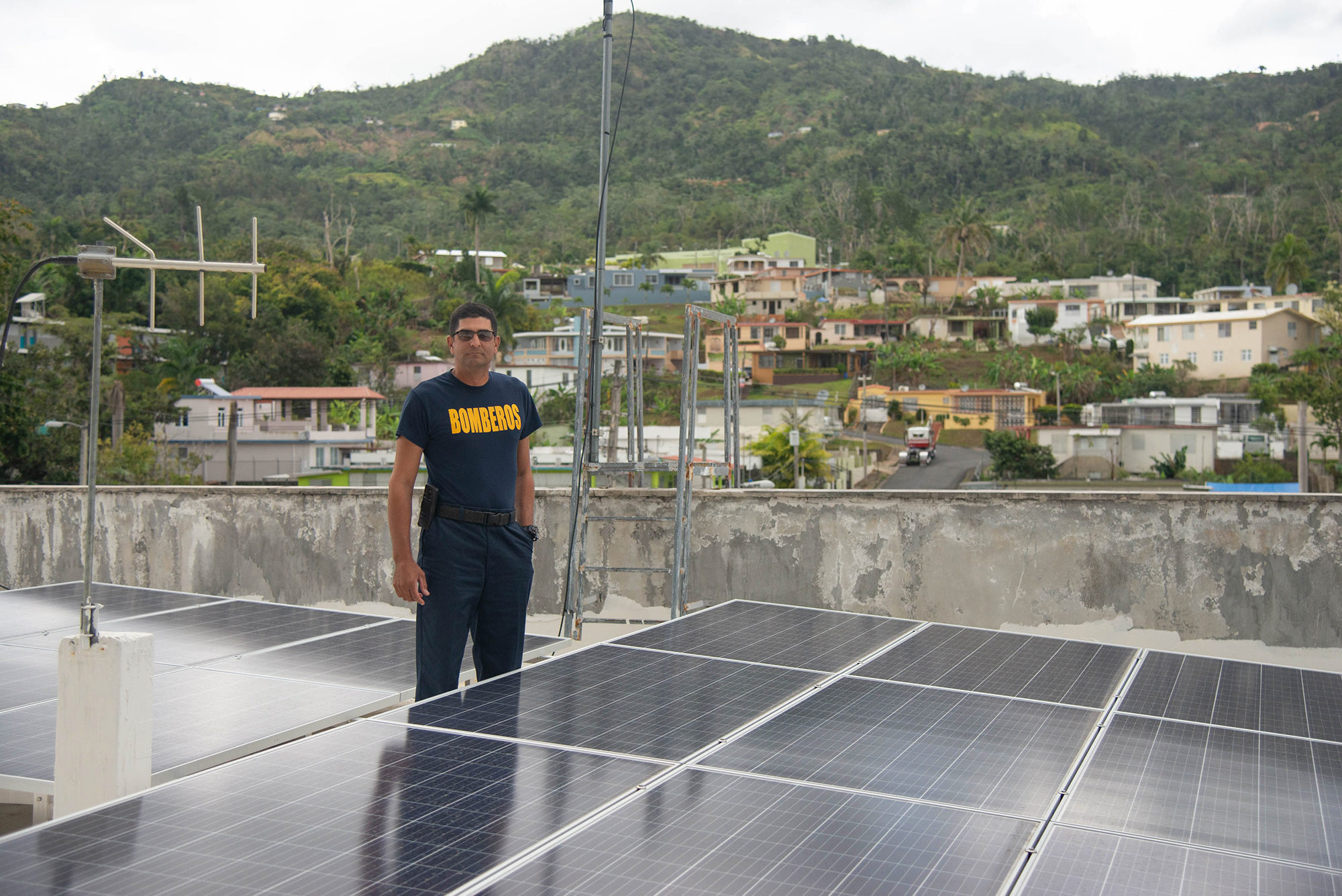 Adjuntas Fire Chief Francisco Hoyos with the fire station's rooftop solar panels. Photo by Valerie Welch