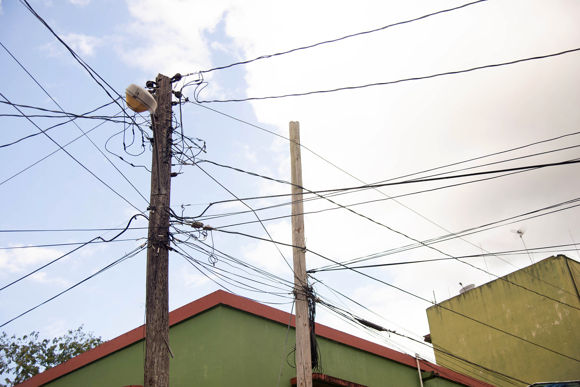Electrical service reaches home from a tangle of lines in Adjuntas. Photo by Valerie Welch